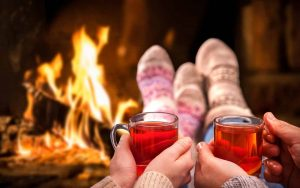 couple drinking in front of fire